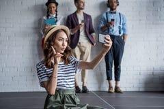 Femme élégante prenant le selfie sur le smartphone tandis que ses amis à l'aide des dispositifs numériques Photo libre de droits