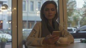 Femme élégante s'asseyant dans le café, le thé potable et les emails de réponse sur le smartphone banque de vidéos