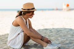Femme élégante s'asseyant sur une plage sablonneuse à l'été Photo libre de droits