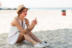 Femme élégante s'asseyant sur une plage sablonneuse à l'été Photos stock