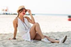 Femme élégante s'asseyant sur une plage sablonneuse à l'été Photographie stock libre de droits