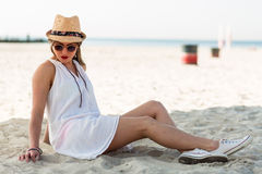 Femme élégante s'asseyant sur une plage sablonneuse Photo libre de droits