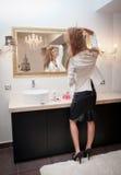 Femme élégante sensuelle dans l'équipement de bureau regardant dans un grand miroir. Belle et sexy jeune femme blonde utilisant un Image stock