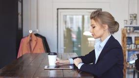 Femme élégante tenant un café et un comprimé dans le bureau moderne clips vidéos