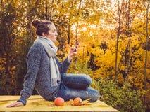 Femme élégante tenant un téléphone portable et s'asseyant sur la terrasse photographie stock libre de droits