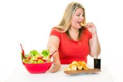 Femme éloignant la salade et mangeant de la nourriture industrielle Image libre de droits