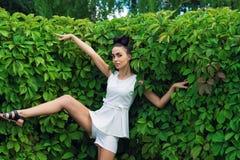 Femme émotive expressive près de bordure de haies verte photo libre de droits