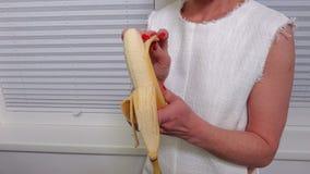 Femme épluchant la banane avant la consommation banque de vidéos