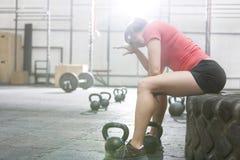 Femme épuisée s'asseyant sur le pneu dans le gymnase de crossfit Image libre de droits