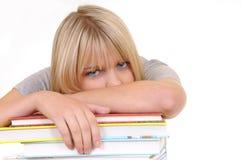 Femme épuisée sur une pile de livres Photos stock