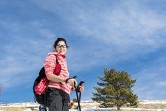 Femme équipée trimardant dans une haute montagne Photos stock