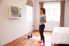 Femme établissant à la forme physique DVD à la TV dans la chambre à coucher photo libre de droits
