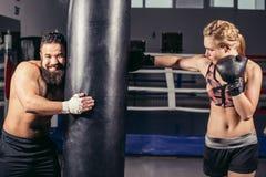 Femme établissant avec les gants et le sac de sable de boxe avec son entraîneur Photographie stock libre de droits