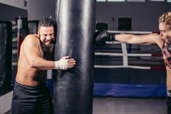 Femme établissant avec les gants et le sac de sable de boxe avec son entraîneur Photographie stock