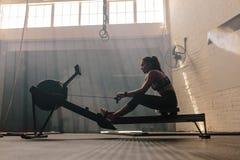 Femme établissant sur une machine à ramer au gymnase photographie stock libre de droits