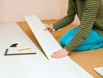 Femme étendant le plancher en stratifié Images stock