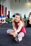 Femme étirant l'exercice tandis qu'amis s'asseyant à l'arrière-plan Images stock