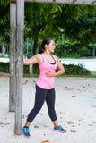 Femme étirant le bras par le poteau en bois en parc d'exercice photographie stock libre de droits