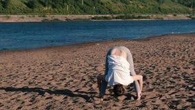 Femme étirant le yoga sur la plage par la rivière dans la ville Belle vue banque de vidéos