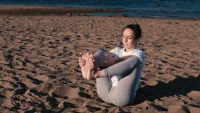 Femme étirant le yoga sur la plage par la rivière dans la ville Belle vue clips vidéos