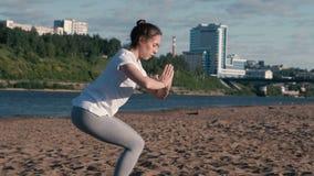Femme étirant le yoga sur la plage par la rivière dans la ville Belle vue de ville clips vidéos