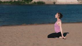 Femme étirant le yoga sur la plage par la rivière dans la ville Belle vue de ville Exercice de respiration clips vidéos