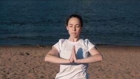 Femme étirant le yoga sur la plage par la rivière dans la ville Belle vue de ville Pose de Namaste banque de vidéos