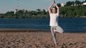 Femme étirant le yoga sur la plage par la rivière dans la ville Belle vue de ville Pose de Vrikshasana banque de vidéos