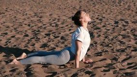 Femme étirant le yoga sur la plage par la rivière dans la ville Belle vue Vinyasa banque de vidéos