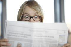 Femme étonné avec des glaces affichant un journal Photos libres de droits