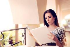 Femme étonnée choisissant du menu de restaurant Image libre de droits