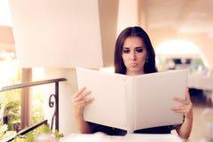 Femme étonnée choisissant du menu de restaurant Photos libres de droits