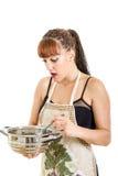 Femme étonnée dans la cuisine remuant le pot photos stock
