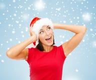 Femme étonnée dans le chapeau d'aide de Santa Photos stock