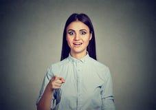 Femme étonnée dirigeant le doigt regardant l'appareil-photo dans l'étonnement photo stock