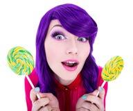 Femme étonnée drôle avec les cheveux pourpres tenant l'OIN de deux lucettes Photos stock