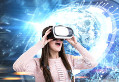 Femme étonnée en verres de VR dans la ville, HUD Earth images libres de droits