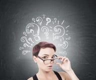 Femme étonnée enlevant des verres, points d'interrogation photographie stock