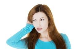 Femme étonnée essayant à l'écoute un bavardage Image libre de droits