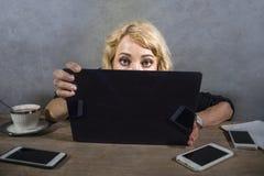 Femme étonnée et soumise à une contrainte de jeunes d'affaires au bureau semblant intense à l'écran d'ordinateur entouré par des  photos stock