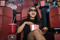 Femme étonnée observant le film 3d Photo stock