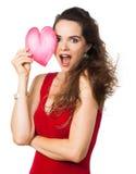 Femme étonnée retenant un coeur d'amour au-dessus d'oeil. Photographie stock