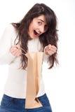 Femme étonnée retenant un sac à provisions et regardant à l'intérieur photos libres de droits