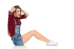Femme étonnée s'asseyant sur le plancher Photo stock