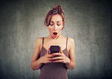Femme étonnée stupéfaite recevoir le message textuel inattendu à son téléphone portable image stock