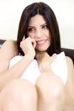 Femme étonnante au téléphone avec le boyfrend se reposant sur le lit étreignant un oreiller Photographie stock libre de droits