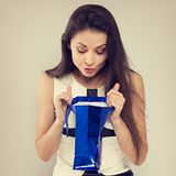 Femme étonnante enthousiaste regardant dans le sac bleu de cadeau avec le sourire sur le fond bleu Bonnes fêtes toned image stock