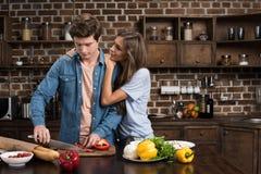 femme étreignant l'ami ce dîner de préparation Photographie stock libre de droits