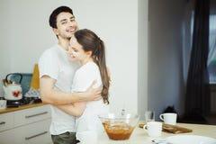 Femme étreignant l'homme dans la salle à manger Ustensiles de cuisine autour de eux Images libres de droits