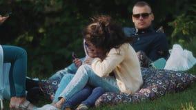 Femme étreignant sa fille tout en se reposant sur un fauteuil poire dehors en parc banque de vidéos